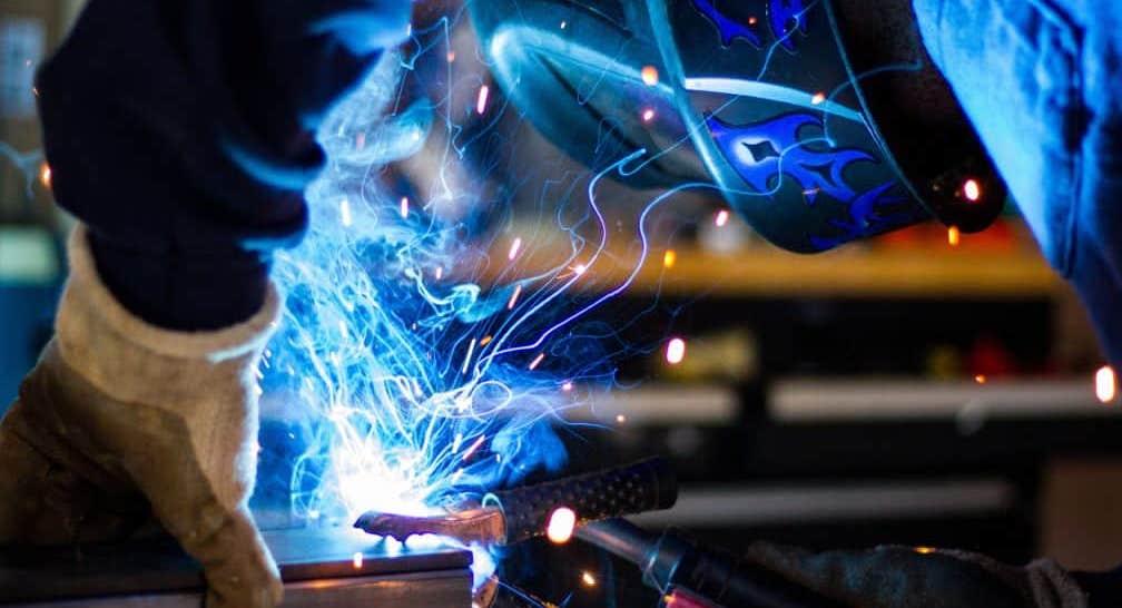 welder with mask making sparks