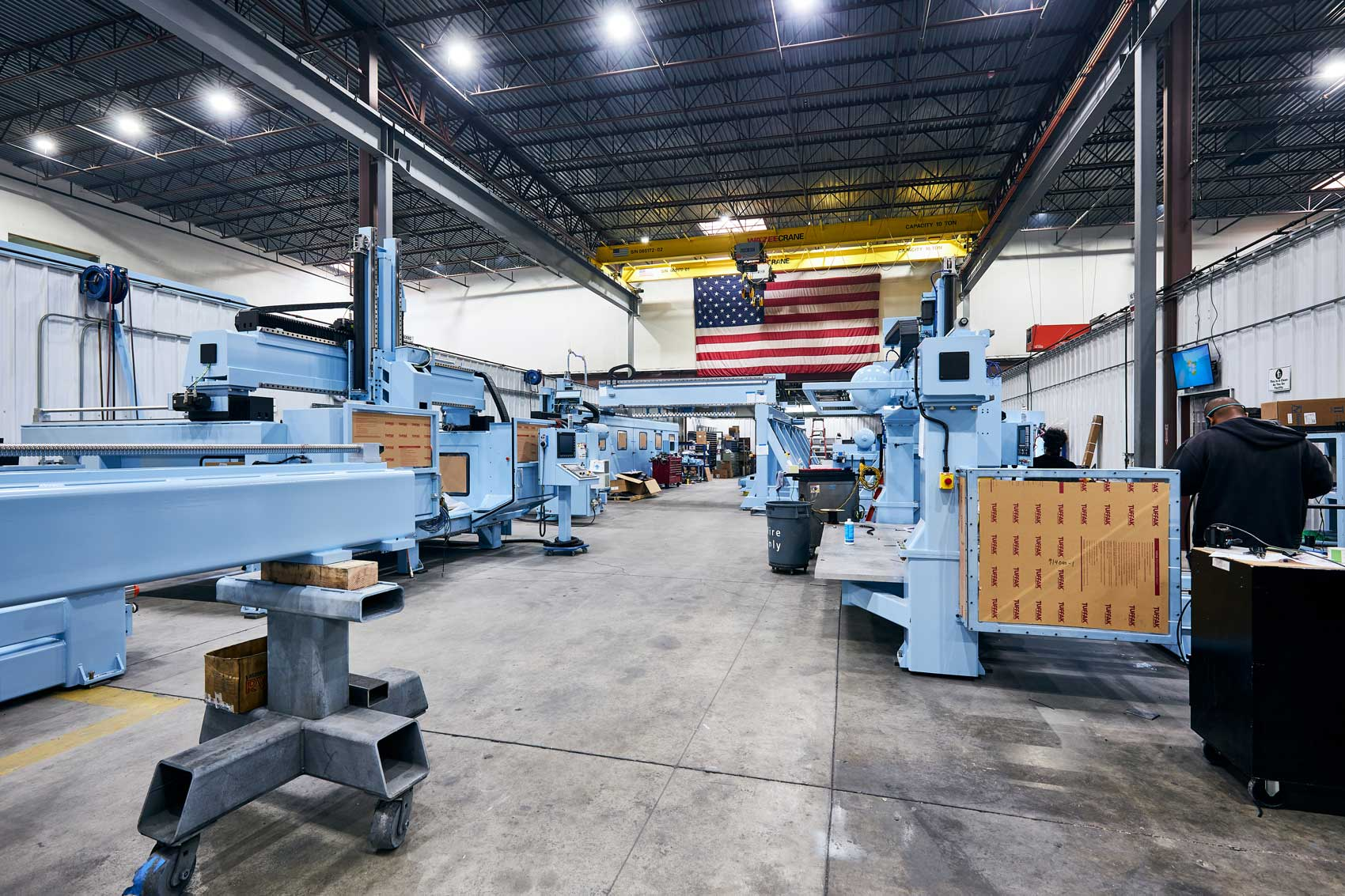 Diversified Machine Systems' Factory floor with blue machines and large American flag