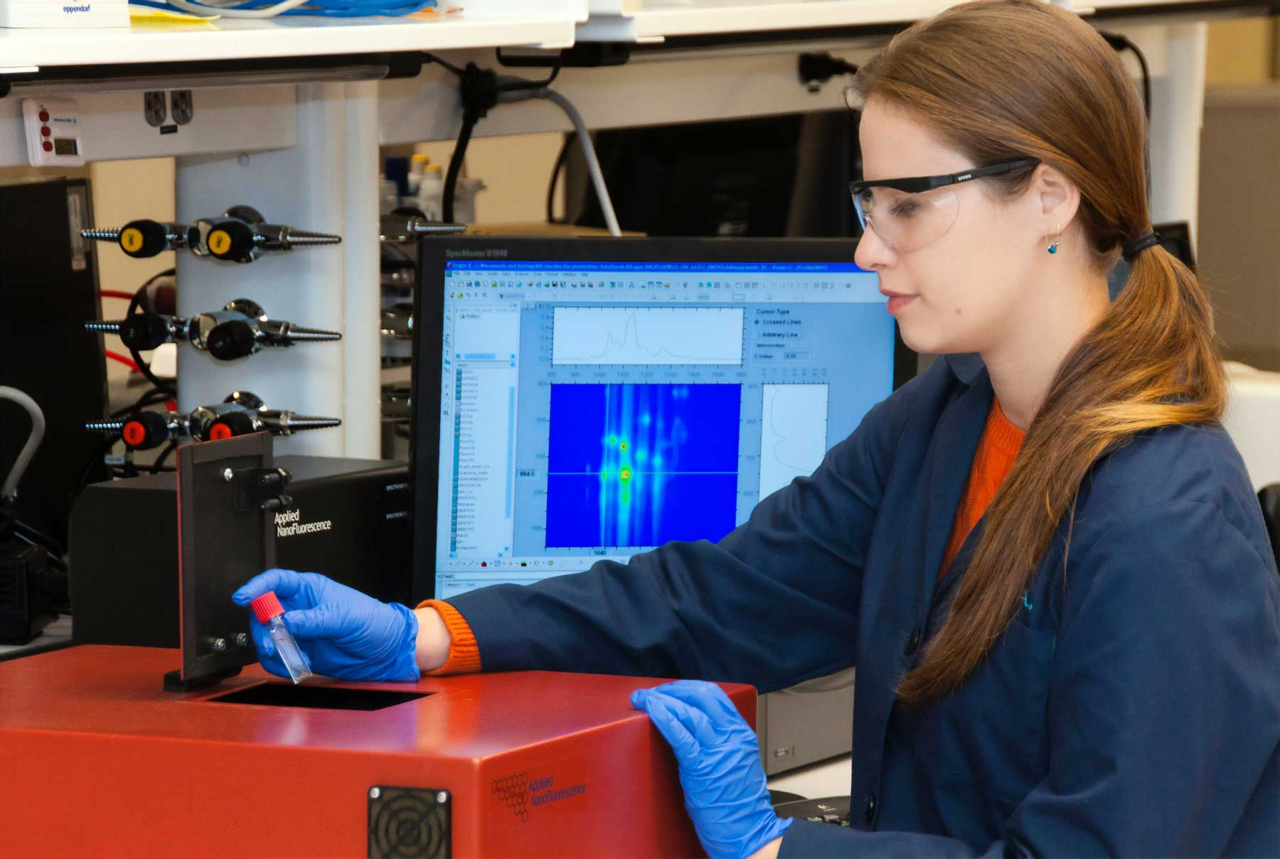 Lab tech in gloves and glasses working with a sample