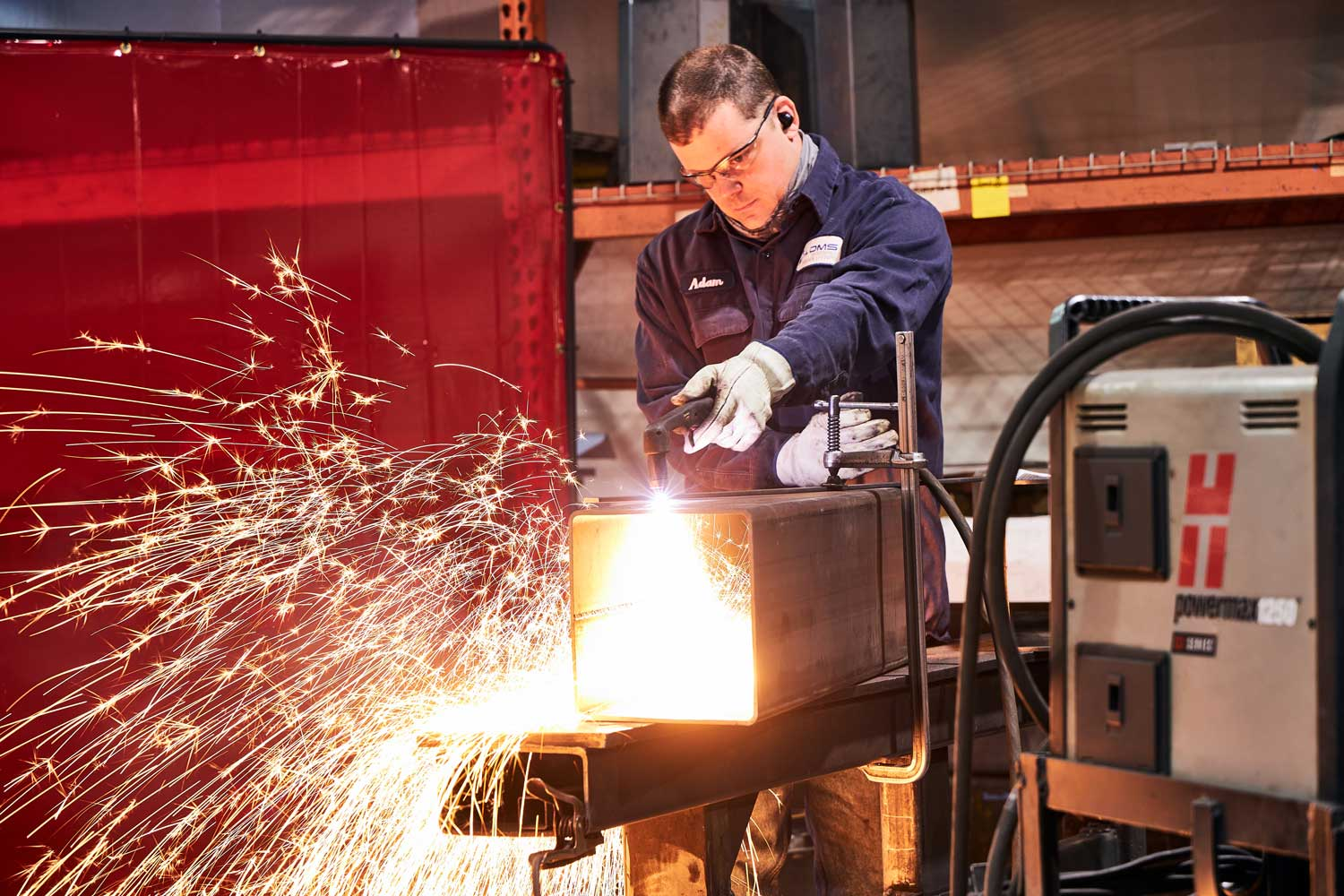 Man welding in DMS uniform with sparks flying