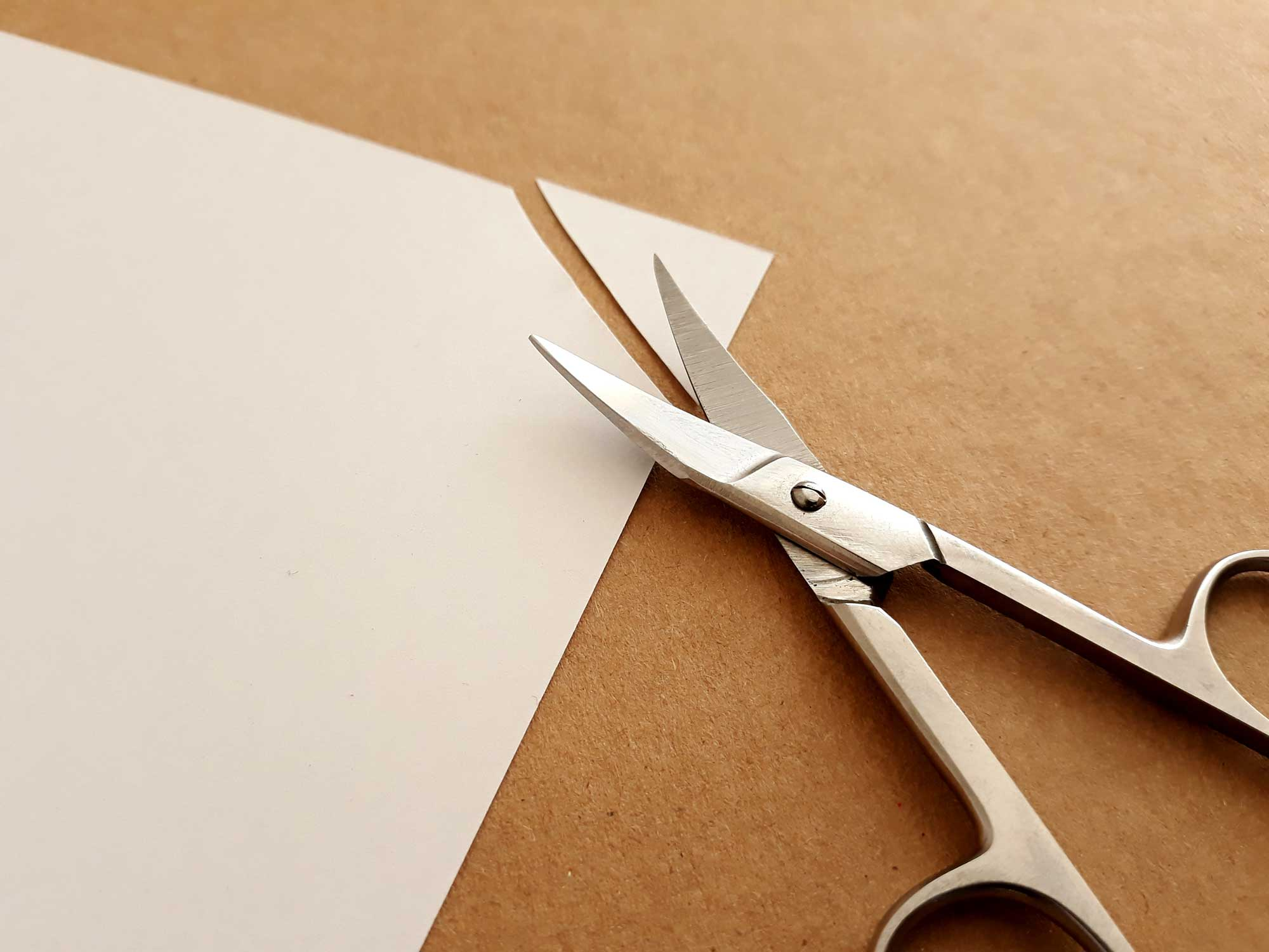 Scissors cutting corners off a page